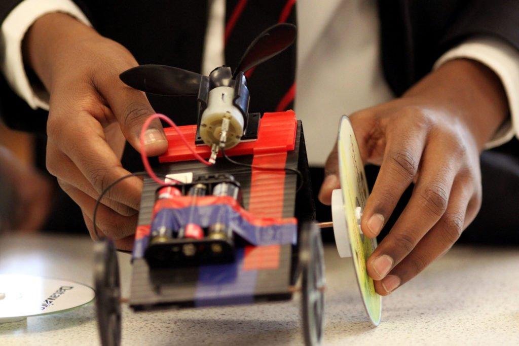 Hands building a fan-powered car