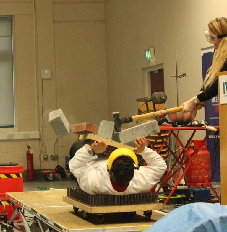 Peter being smacked with a sledge hammer while laying on a bed of nails